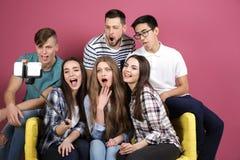 Jeunes amis prenant le selfie tout en se reposant sur le sofa Image libre de droits