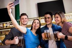 Jeunes amis prenant le selfie tout en tenant la tasse de bière Image stock