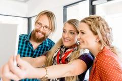 Jeunes amis prenant Selfie dans le bureau Photo stock
