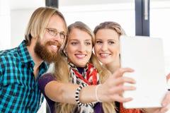 Jeunes amis prenant Selfie dans le bureau Photographie stock