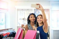 Jeunes amis prenant un selfie dans un magasin d'habillement Photographie stock