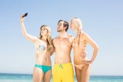 Jeunes amis prenant un selfie sur la plage Images libres de droits