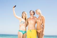 Jeunes amis prenant un selfie sur la plage Images stock