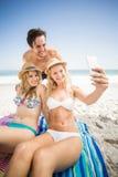 Jeunes amis prenant un selfie sur la plage Image stock