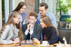 Jeunes amis réfléchis ayant une concurrence d'échecs sur un fond de café Concept d'amitié Images stock