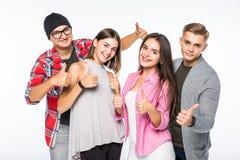 Jeunes amis réussis heureux montrant le pouce d'isolement sur le fond blanc Images stock