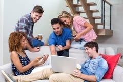 Jeunes amis regardant dans l'ordinateur portable tout en se reposant sur le sofa Photographie stock libre de droits