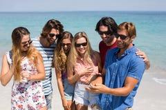 Jeunes amis regardant dans le téléphone portable Image stock