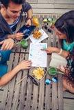 Jeunes amis regardant la carte au-dessus d'une table Photo stock