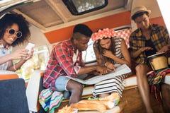 Jeunes amis regardant la carte dans le camping-car Photos libres de droits
