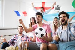 Jeunes amis regardant la TV et encourageant le football Image stock