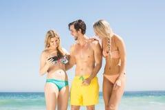Jeunes amis regardant le téléphone portable sur la plage Images libres de droits
