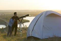 Jeunes amis regardant par le télescope sur la colline l'ev d'été Photographie stock libre de droits