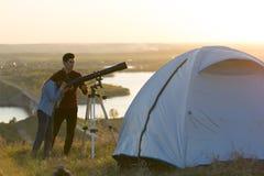 Jeunes amis regardant par le télescope sur la colline l'ev d'été Photo libre de droits