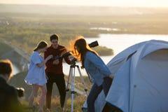 Jeunes amis regardant par le télescope sur la colline la soirée d'été - voyageurs touristiques Images stock
