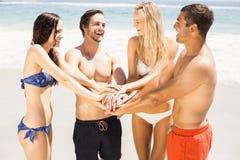 Jeunes amis remontant leurs mains sur la plage Images stock