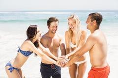 Jeunes amis remontant leurs mains sur la plage Photo libre de droits