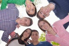 Jeunes amis restant ensemble extérieurs en parc Images libres de droits