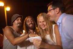 Jeunes amis riant de ce qu'elles voient sur le mobile Images libres de droits