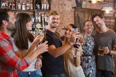 Jeunes amis riant ensemble tout en se tenant boit Images libres de droits