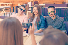 Jeunes amis riant et prenant la photo en café Photo libre de droits