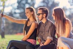 Jeunes amis riant et prenant le selfie dehors Image libre de droits