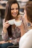 Jeunes amis riant tout en buvant du café Photos stock