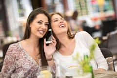 Jeunes amis riant tout en buvant du café Photographie stock