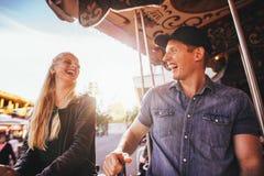 Jeunes amis riants montant sur le carrousel Photographie stock libre de droits