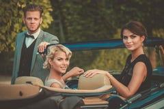 Jeunes amis riches dans un convertible classique Photographie stock