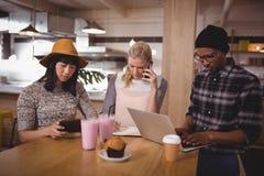 Jeunes amis s'asseyant à la table tout en employant des technologies Image libre de droits