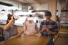 Jeunes amis s'asseyant avec des casques de réalité virtuelle au café Photos stock