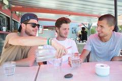 Jeunes amis s'asseyant dans la barre ayant la boisson Photo libre de droits