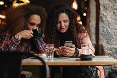 Jeunes amis s'asseyant dans un café regardant un smartphone Images stock