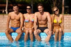 Jeunes amis s'asseyant par le sourire de piscine Photos libres de droits