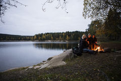 Jeunes amis s'asseyant près du feu par le lac au crépuscule Image libre de droits