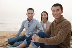 Jeunes amis s'asseyant sur la plage, souriant et regardant l'appareil-photo Photos libres de droits