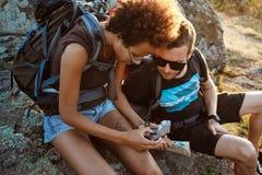 Jeunes amis s'asseyant sur la roche en canyon, regardant la boussole Image stock