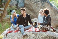 Jeunes amis s'asseyant sur la roche en canyon, souriant, thé potable Photos stock
