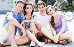 Jeunes amis s'asseyant sur la rue image libre de droits