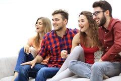Jeunes amis s'asseyant sur le divan et s'enracinant pour leur équipe préférée Photo libre de droits