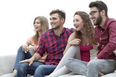 Jeunes amis s'asseyant sur le divan et s'enracinant pour leur équipe préférée Photographie stock libre de droits