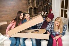 Jeunes amis s'asseyant sur le sofa et la boîte s'ouvrante avec la guitare Photo libre de droits