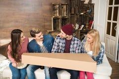Jeunes amis s'asseyant sur le sofa et tenant la grande boîte Images libres de droits