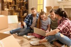 Jeunes amis s'asseyant sur le tapis et à l'aide de l'ordinateur portable dans la nouvelle maison Images libres de droits