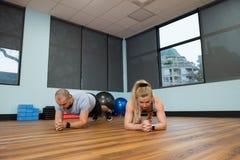 Jeunes amis s'exerçant sur le plancher en bois dur Images stock