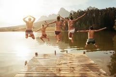Jeunes amis sautant dans le lac d'une jetée Image stock