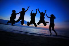Jeunes amis sautant sur la plage Photos libres de droits
