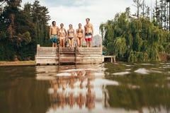 Jeunes amis se tenant sur la jetée au lac Photos stock