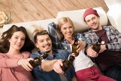 Jeunes amis se trouvant sur le sofa avec des bouteilles à bière et souriant à l'appareil-photo Photographie stock